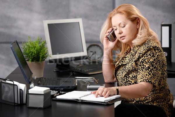 Altos mujer llamando oficina sesión Foto stock © nyul