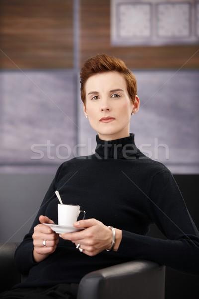 Smart woman having coffee in armchair Stock photo © nyul
