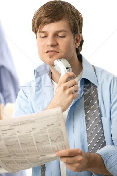Férfi elektromos borotva fiatalember olvas újság Stock fotó © nyul