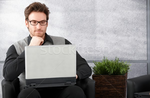 Young man browsing internet on laptop Stock photo © nyul