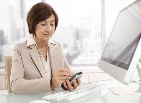 Senior professional woman using pda in office Stock photo © nyul