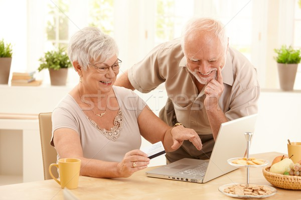 Stock photo: Happy older couple doing online shopping