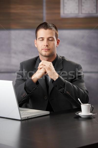 Businessman meditating at desk Stock photo © nyul