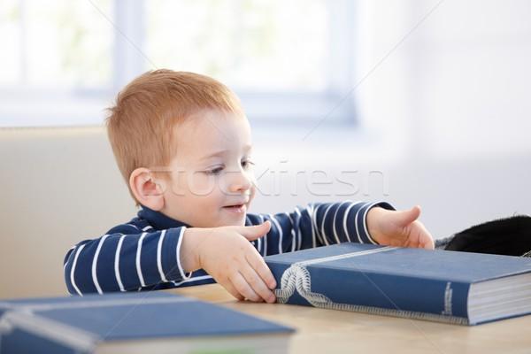 Pequeno menino enciclopédia olhando tabela sorridente Foto stock © nyul