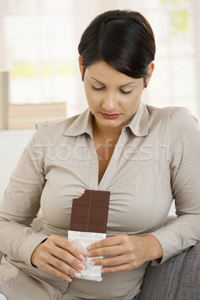 Woman looking guiltily to chocolate Stock photo © nyul