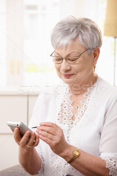 Anziani signora smartphone home donna sorriso Foto d'archivio © nyul