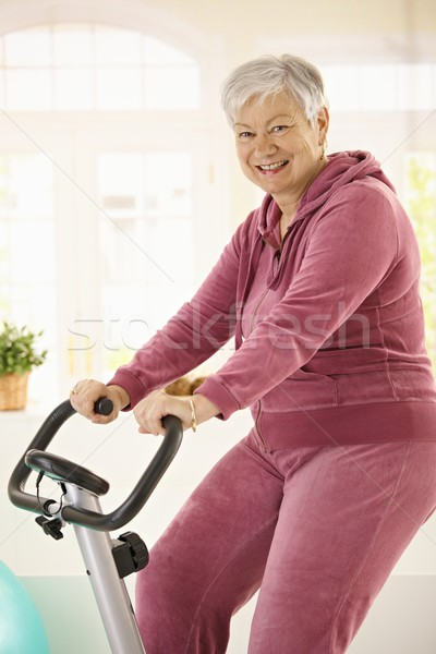 Healthy elderly woman on exercise bike Stock photo © nyul