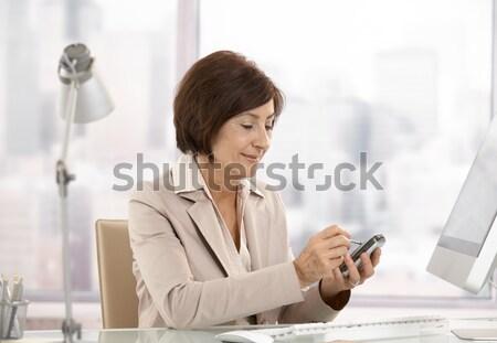 Maturo femminile executive smartphone ufficio sorridere Foto d'archivio © nyul