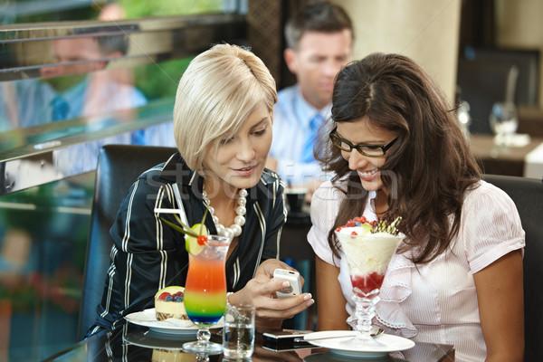 Giovani donne cafe seduta dolci guardando cellulare Foto d'archivio © nyul