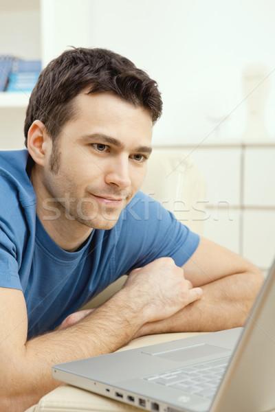 Jonge man met behulp van laptop home gelukkig leggen sofa Stockfoto © nyul