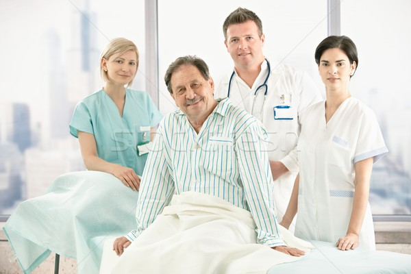 Stock photo: Older patient on bed with hospital crew
