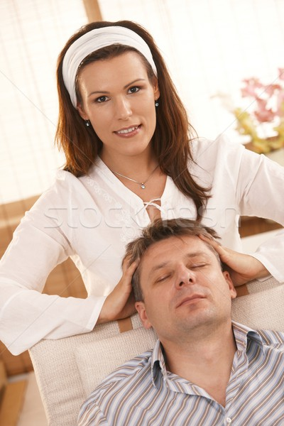 Stock photo: Attractive woman giving head massage to man