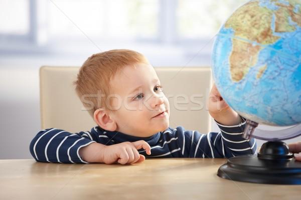 Little scholar studying globe smiling Stock photo © nyul