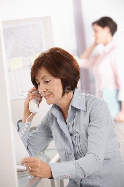 Mature office worker woman using landline phone Stock photo © nyul