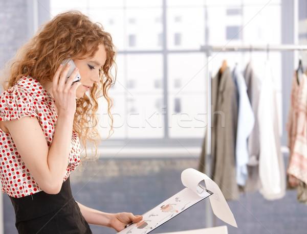 Pretty fashion designer in work using mobile phone Stock photo © nyul