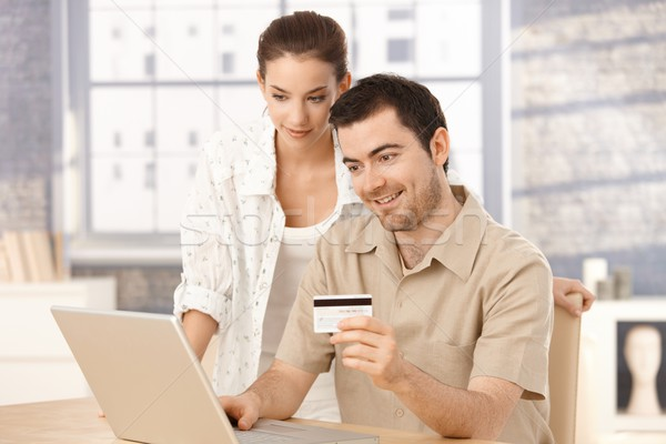Happy couple shopping online at home smiling Stock photo © nyul