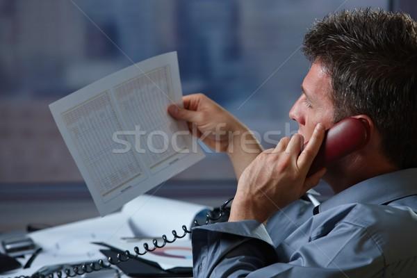 Businessman on phone checking document Stock photo © nyul