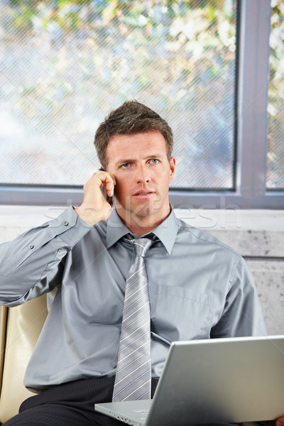 Stock photo: Businessman on call with laptop on sofa