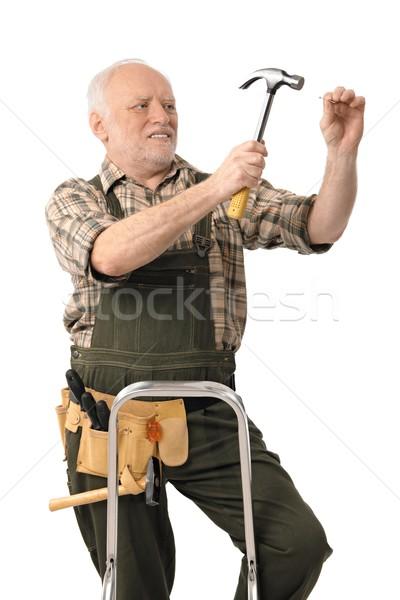 Elderly handyman hammering nail Stock photo © nyul