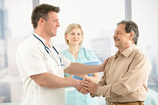 Doctor shaking hands with senior patient Stock photo © nyul