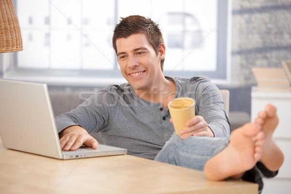 śmiechem młody człowiek domu za pomocą laptopa Zdjęcia stock © nyul