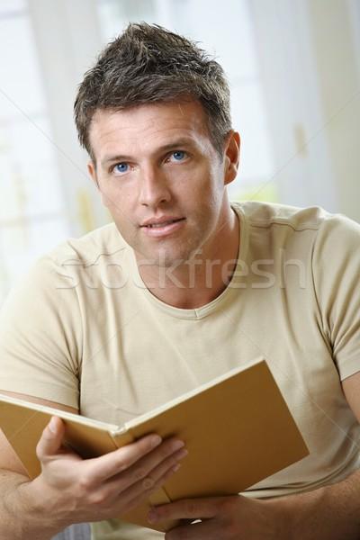 Hombre libro mirando cámara casa sesión Foto stock © nyul