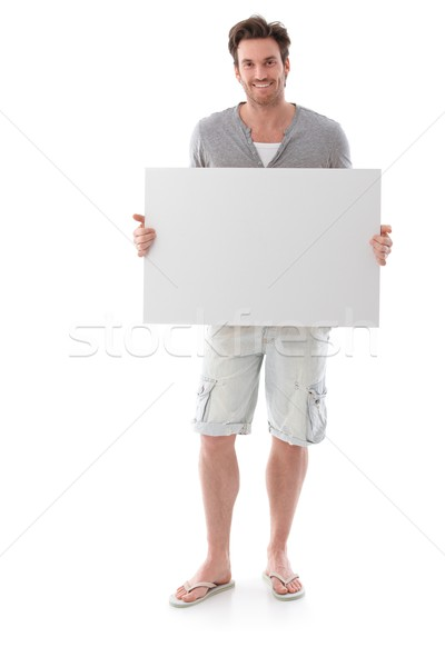 Happy man holding blank sheet smiling Stock photo © nyul