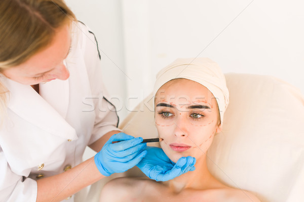 Doctor drawing marks on female face Stock photo © O_Lypa