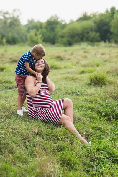 Boy kissing his pregnant mother. Stock photo © O_Lypa
