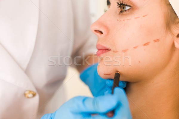 Stock photo: Hand in glove marking women face.