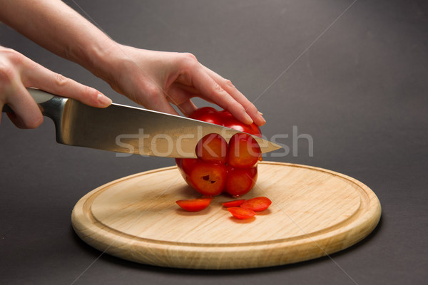 Woman slices red pepper on chopping board Stock photo © O_Lypa