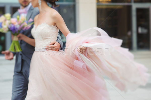 Luxury bride holding a flying dress and walking Stock photo © O_Lypa