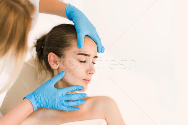 Doctor hands in gloves touching woman face Stock photo © O_Lypa