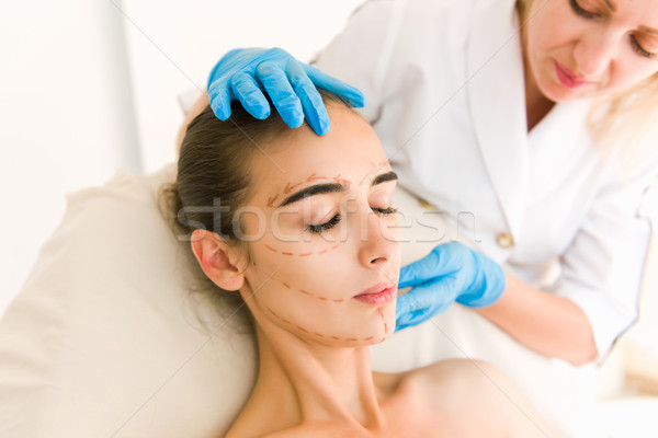 Doctor checking woman's skin before plastic surgery Stock photo © O_Lypa