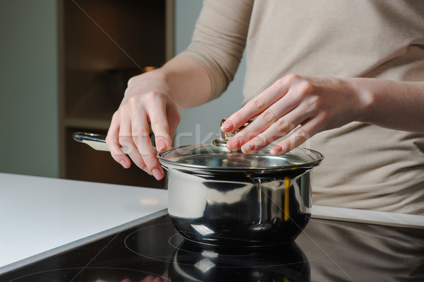 Person removing lid from cooking pot Stock photo © O_Lypa