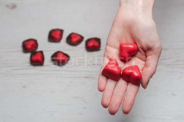 Kezek tele csokoládé édesség piros szívek Stock fotó © O_Lypa