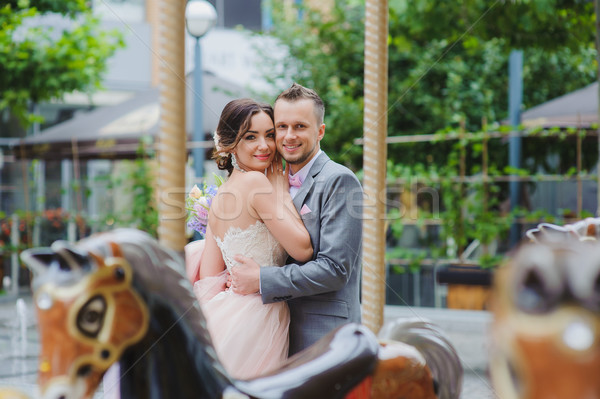Happy newlyweds huging near the carousel Stock photo © O_Lypa