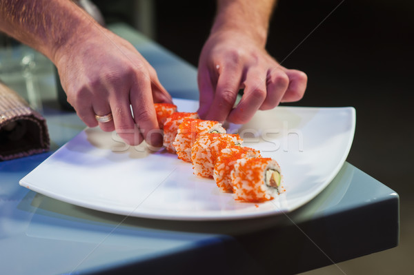 Cook serving california roll on white plate. Stock photo © O_Lypa