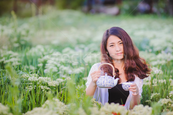 Young Chinese girl pouring tea in flowering meadow Stock photo © O_Lypa