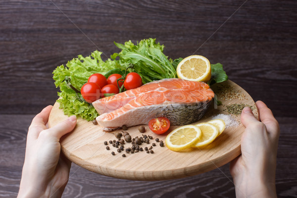 Woman holding a wooden plank with raw salmon Stock photo © O_Lypa