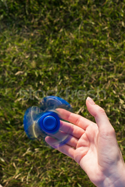 Hand of girl holding fidget spinner. Stock photo © O_Lypa