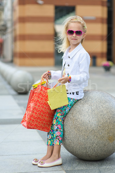 Young little girl with full shopping bags. Stock photo © O_Lypa