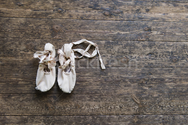 Stock photo: Old ballet shoes on old wooden floor.