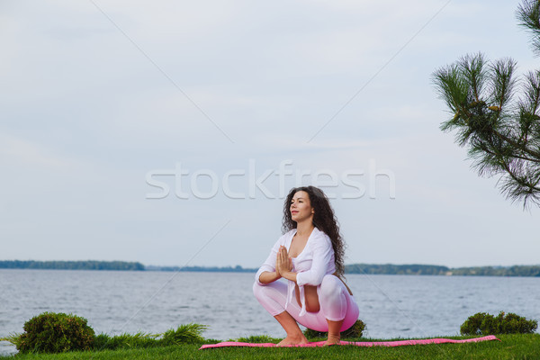 Pregnant woman is practicing yoga beside river Stock photo © O_Lypa