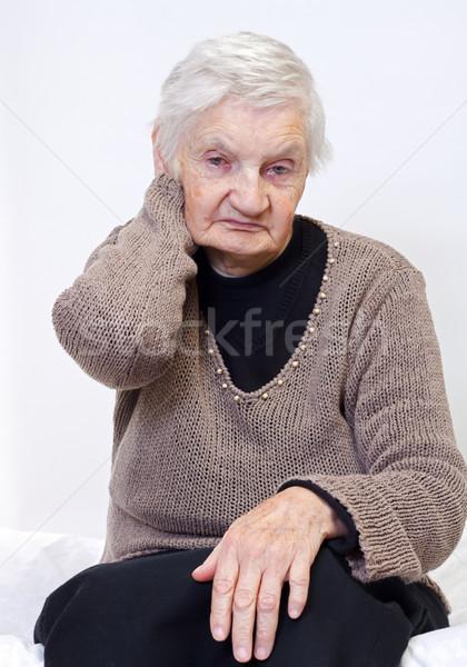 Nyugdíjas élet idős nő ül ágy nő Stock fotó © ocskaymark
