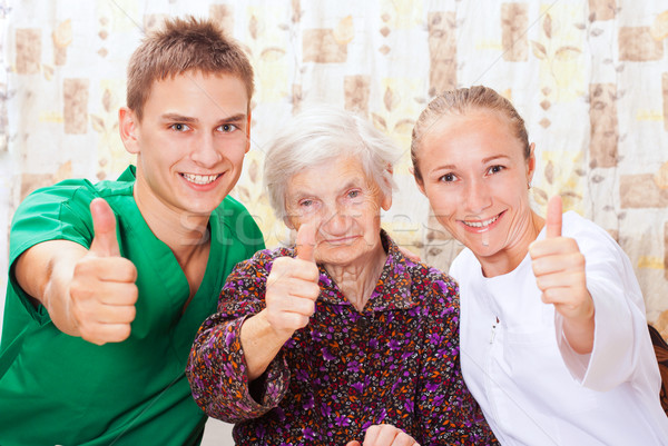 Elderly woman with the young doctors Stock photo © ocskaymark