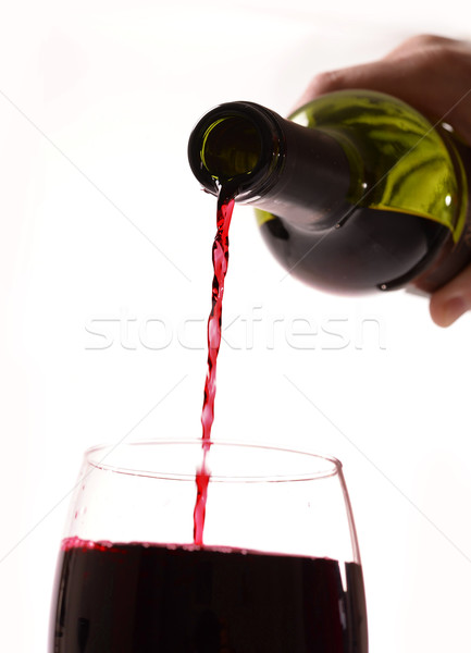 Man Hand holding Bottle filling Glass with Red Wine Stock photo © ocusfocus