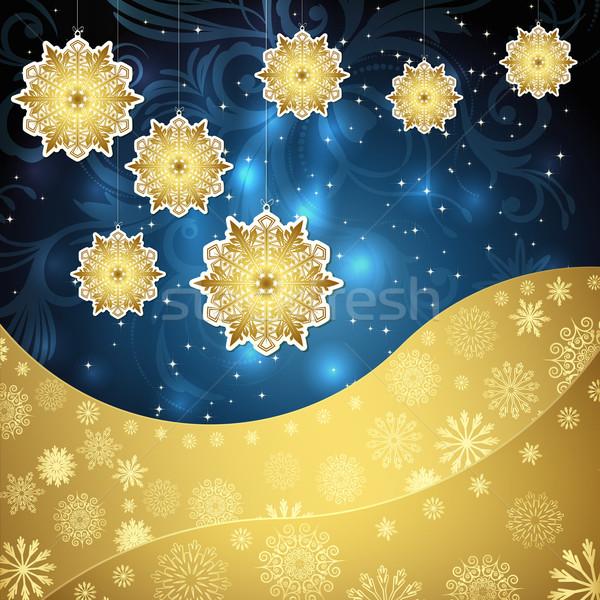 Golden snowflakes and frosty patterns on a dark blue background. Stock photo © OlgaYakovenko