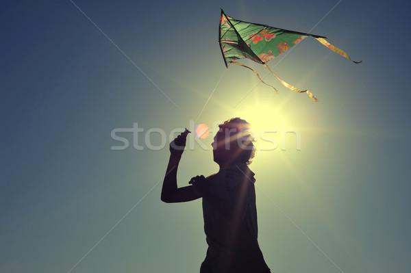 Boy flying a kite on beach at sunrise  Stock photo © orla