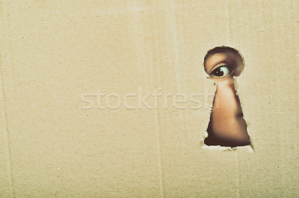 Eye looking through a conceptual keyhole on cardboard, close up Stock photo © orla